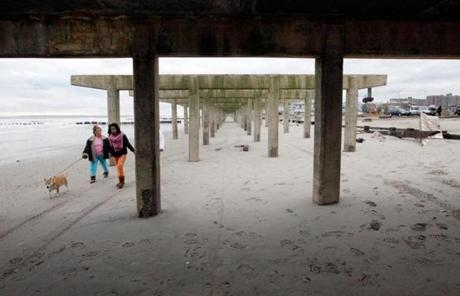 Two people walked a dog under what was left of the boardwalk at Rockaway Beach.