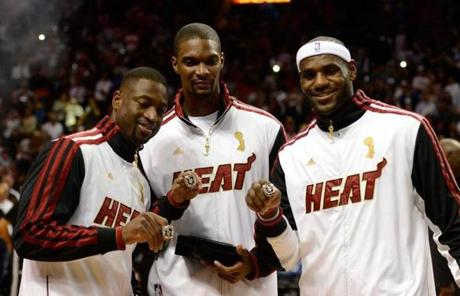 Wade, Chris Bosh, and James posed with their championship rings before the game.