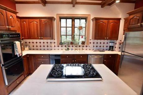 The updated kitchen has white marble counters, cherry cabinets, cooking island, and decorative ceiling beams.
