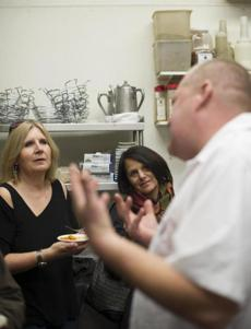 Debbie Dollivar, of Martha's Vineyard, left, and Cori Pasqaule, of Old Saybrook, Ct., listen to chef Kevin Fitzgerald inside the kitchen of Sardella's, the last stop on the Newport Gourmet Tour in Newport, Rhode Island, Saturday, Nov. 3, 2012. Gretchen Ertl for the Boston Globe