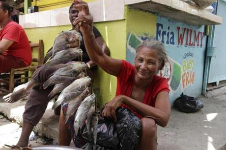 A fishmonger shows her wares at the market in the small coastal town of Paraíso (Spanish for paradise), in the Barahona province.