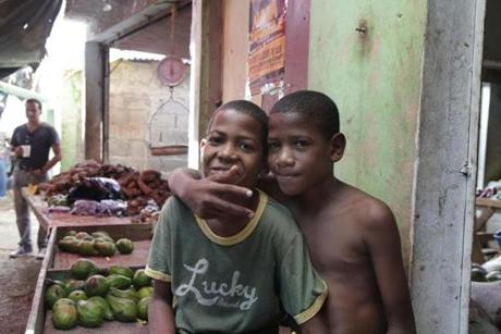 Boys pose outside a vegetable market stall in the small coastal town of Paraíso (Spanish for paradise), in the Barahona province.