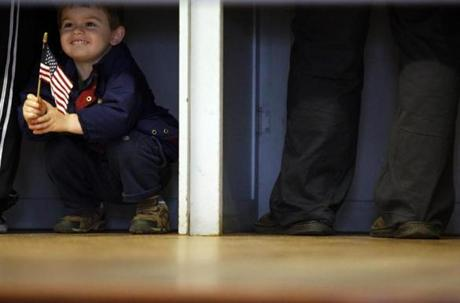 A boy peeked out of the voting booth  in New Hampton, N.H.
