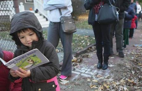 "Alice Vu, 5, read ""The Hungry Kitten,"" while waiting outside a polling station on Lexington Avenue in Cambridge."