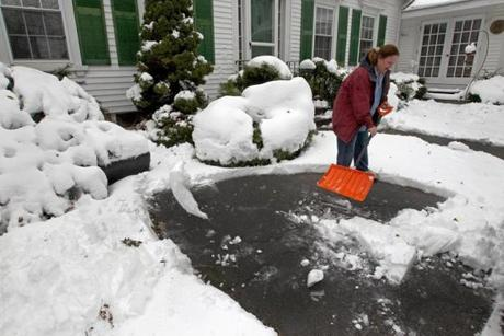 Mary O'Dea shoveled off her Pleasant Street driveway as the nor'easter brought early snow to Foxborough.