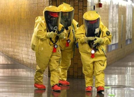 Three Boston firefighters in hazmat suits walked to a trolley car at the Bowdoin T station to inspect a suspicious bio-hazard device during the citywide Urban Shield training exercises.