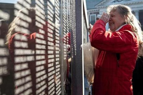 Barbara Casey examines her father's name on the new monument on Woburn Common, which currently lists 11,665 city residents who served in the military during wartime.