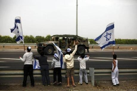 Israeli children waved their national flag as an army convoy passed on a road leading to the Israel-Gaza border near the southern Israeli town of Ofakim on Saturday.
