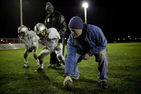 Volunteer coach Ray Vega hiked the ball during the Boston Raiders football practice in Dorchester