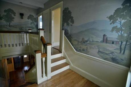 Pastoral murals line the central staircase.