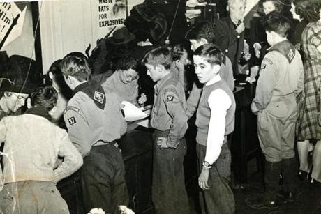November 30 1942 / So great was the confusion following the Cocoanut Grove tragedy that the identity of many of the victims is still unknown. At the hastily set up information desk at 9 Park St. at the Commission on Public Safety, Boy Scouts lined up to serve as couriers with the duty of carrying printed information to relatives of the victims who were waiting there.