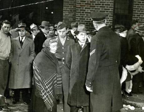 November 30 1942 / An elderly woman sought news of her son from Sergeant Joseph E. Green of the Boston Police Department outside the Northern Mortuary on North Grove Street. Extra details of 200 police were assigned for 24-hour duty handling crowds at the Northern and Southern Mortuaries. Only those people who could claim a relative missing and knew of some ring or trinket or bit of clothing which might serve as identification were allowed in the morgues.