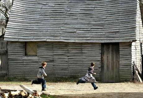 Plymouth 11/2112- Hundreds of visitors came to Plimouth Plantation a day before Thanksgiving. In the 1627 English village, ayoungsters run past one of the homes. Boston Globe staff photo by John Tlumacki (metro)