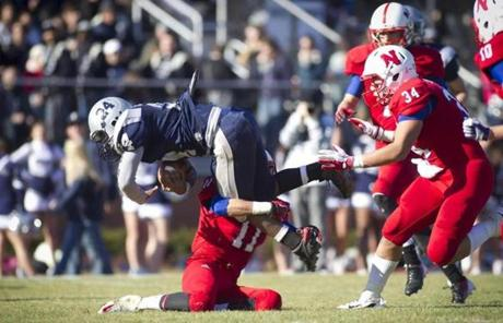 Framingham's Raphael Lanzo was tackled by Natick's Mike Abbruzzese. Natick won, 26-14.