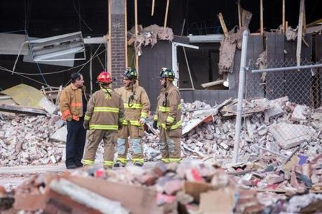 Firefighters stood at the scene of the explosion.