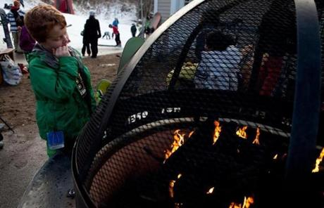 Shaun McCarty, 9, warmed himself by the fire as temperatures started to fall.
