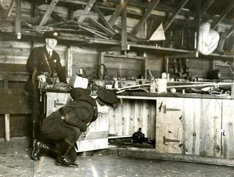 May 10, 1935:  Repeal of Prohibition in Massachusetts didn't end the smuggling of liquor, in this case, to avoid paying liquor taxes. Here, Federal agents and state troopers examined a carpenter's bench at the Sea View Poultry Farm in Fairhaven, MA on May 10th because of a strong odor of alcohol. They uncovered 2500 cases of