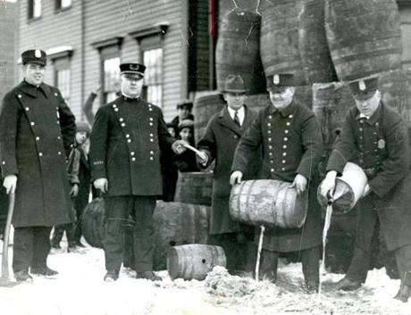 Cambridge Officer Patrick F. Ready had his ax in hand as the police liquor raiding party poured illicit liquor down an East Cambridge sewer. Others in the photo, (from left) are Captain Timothy Leahy, an unidentified prohibition agent, Officer Fred Collins and Officer Timothy Callahan.