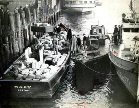 January 18, 1932: Two high-powered boats were seized in Boston Harbor. The first boat to be captured was the Mary on the left. The Mary was driven aground off Commercial Point, near Victory road, Neponset. The crew fled. The Buddy (middle) was captured when the Coast Guard patrol boat came upon the boat in the fog. All members of the crew were taken with it and the haul represented one of the largest seizures of whisky in months. The total value of the two boats, plus their liquor cargoes was estimated at about $175,000.