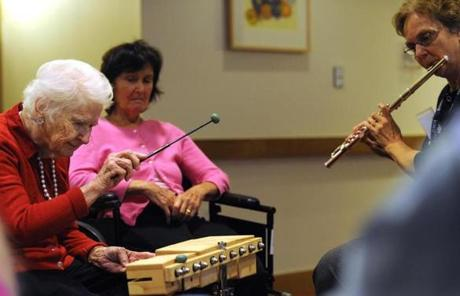 Dorothy, a resident of New Bridge on the Charles Assisted Living in Dedham, played a percussion instrument to accompany therapist Sally Harrison during a music session for Alzheimer's patients.