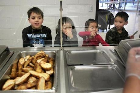 Students (from left) Ravin Bhatia, Jolie Yu, Stephanie Sun, and Grant Keo await lunch at Brookline's Runkle School.