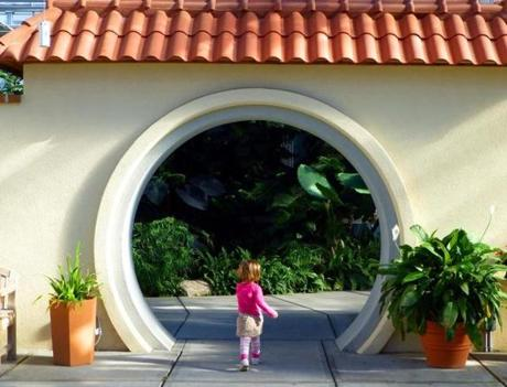 A young girl strides purposefully through an arch inside the Botanical Center at Roger Williams Park.