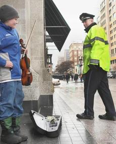 Boston police Officer Dan McMorrow paused to encourage Owen Cunningham, 11, of Dorchester, who played Irish folk tunes for passerbys on Boylston Street in Boston's Back Bay to save up money for an upcoming trip to Ireland with the Congress School of Music in Quincy. Dec. 1,2012.