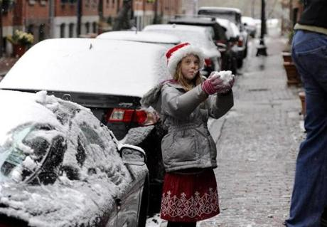 Ella Schweizer, 8, shows her dad, Anthony Schweizer, a ball of snow she made by scraping it off the top of a car as they put up some holiday decorations outside of their South End home.