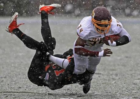 Wayland's Robert Williams brings down Sharon's Tobenna Modebelu in the first half as Wayland took on Sharon in the Div. III High School Super Bowl Championship game at Bentley University in Waltham.