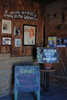 Concert posters, license plates, and quirky signs cover the walls.