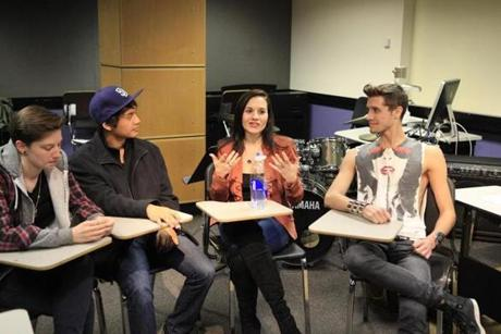 Berklee students John Silos (left) and Stewart Taylor discuss the Hit Songwriting class with their professor, Kara DioGuardi.