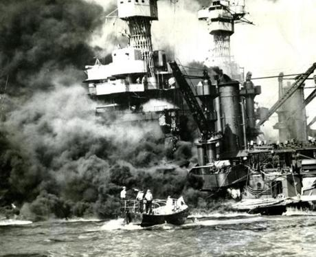 December 7, 1941: This was the scene at Pearl Harbor after the sneak attack on US warships by the Japanese on December 7, 1941. Smoke was seen rolling out of the stricken 31,800 ton USS West Virginia as a small boat goes to the rescue of one of the battleship's seamen (in the water). Two other men could be seen on the superstructure (upper left). The mast of the USS Tennessee could be seen beyond the burning West Virginia.