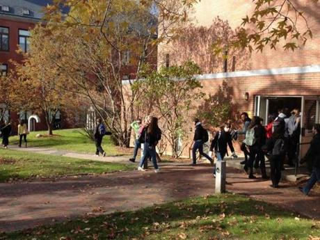 Students exit and enter a dorm in between classes.