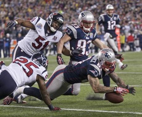 The Patriots' Aaron Hernandez recovered a Stevan Ridley fumble in front of the Texans' Kareem Jackson and Darryl Sharpton during first quarter action.