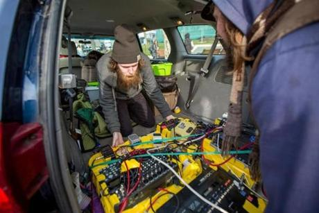Mark Johnson (left), 27 and Adam Kohl (right), 30, of BANG! BROS. moved their equipment into their van in front of Cambridge Town Hall while trying to break the Guinness World Record for most cities played in under 24 hours.