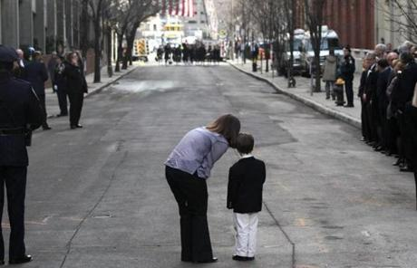 Kevin White's niece, Beth Casey, and her son Tommy waited for the funeral procession of former the former Boston mayor at St. Cecilia Church. Feb. 1, 2012.