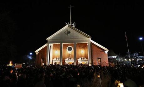 People stand outside a vigil at the Saint Rose of Lima church in Newtown following an attack at the Sandy Hook Elementary School, where a gunman killed 27 people, including 20 children and himself.