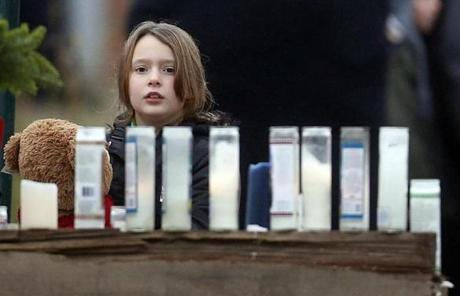 A young girl holding a teddy bear looked at the memorial outside of St. Rose of Lima Roman Catholic Church.
