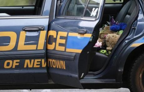 A teddy bear and flowers were in the cruiser of Newtown Police Officer Maryhelen McCarthy.