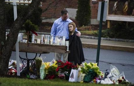 Mourners embraced at a memorial in front of the St. Rose of Lima Catholic church in Newtown Saturday.