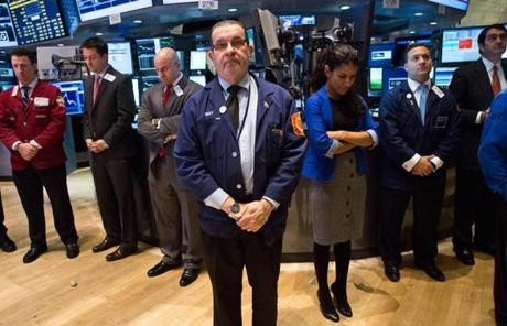 Traders on the floor of the New York Stock Exchange held a moment of silence before trading began on Monday.
