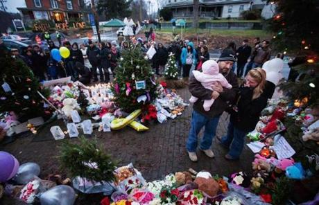 A family embraced at a memorial in Newtown to the victims.