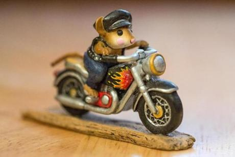 A miniature depicting a mouse on a motorcycle.