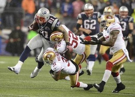 Patriots tight end Aaron Hernandez was tackled by the 49ers' Donte Whitner, bottom, and Patrick Willis in the fourth quarter .