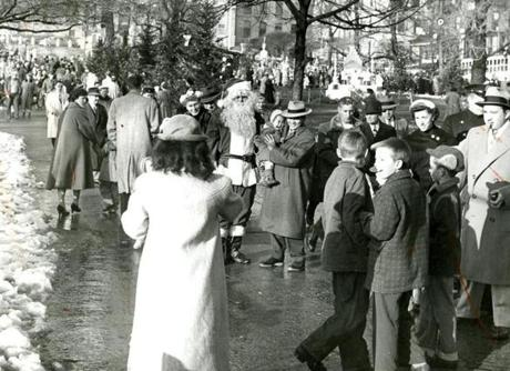 December 16, 1956: Globe Santa attracted a crowd of people wanting to have pictures taken with him. This was the inaugural year of the Boston Globe Santa Claus Fund. The Boston Post started the Santa Fund in 1910. When the Post closed earlier this year, The Boston Globe with Mayor John Hynes continued the long tradition of providing Christmas toys for needy families.