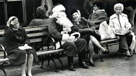 November 28, 1979:  The Jordan Marsh Santa, on his break, got Christmas requests from an older client at Downtown Crossing. Not everyone seemed as enthused to see Santa, however.