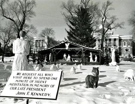December 17, 1963: The Christmas scene on historic Boston Common on this year had this sign set amidst a tableau of a shepherd and his flock. A manger scene is in the center background with the State House at the far right. For the first time the Christmas lights in the State House were not used. Governor Peabody asked that they be turned off during the 30-day period of mourning for the late President John F. Kennedy who was assassinated November 22nd in Dallas, Texas.