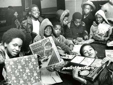 December 16, 1972: Children at the South End Boys Club on Washington Street showed off presents given to them by Santa Claus during one of his stops as part of his Christmas Caravan, which visited three Boston neighborhoods.
