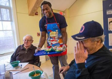 Former Patriots player Eric Alexander, center, served seniors Achot Khoubesserian (left) and Tom Scalese (right) at the Beech Street Center in Belmont.