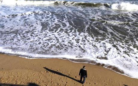 A man looked out at the ocean on Plum Island, where a familiar story played out as another storm rolled in and took its toll of the coastline.